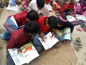 Children reading books sitting on the ground in a village